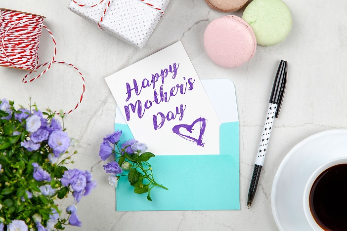 a cluttered desk with a happy mother's day card